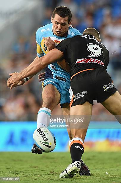 Daniel Mortimer of the Titans is tackled by Robbie Farah of the Tigers during the round one NRL match between the Gold Coast Titans and the Wests...