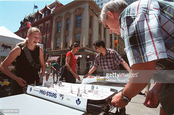 Daniel Moy 6 playing table hockey on Yonge St with dad Danny Dad Brian Thompson from Sudbury doing same with daughter Stephanieflag in hairSlap shot...