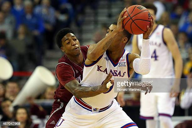 Daniel Mullings of the New Mexico State Aggies defends against Frank Mason III of the Kansas Jayhawks during the second round of the 2015 NCAA Men's...