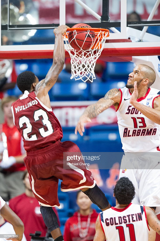Daniel Mullings #23 of the New Mexico State Aggies dunks the ball in front of Mychal Ammons #13 of the South Alabama Jaguars at USA Mitchell Center on December 4, 2012 in Mobile, Alabama. New Mexico State defeated South Alabama 58-52.