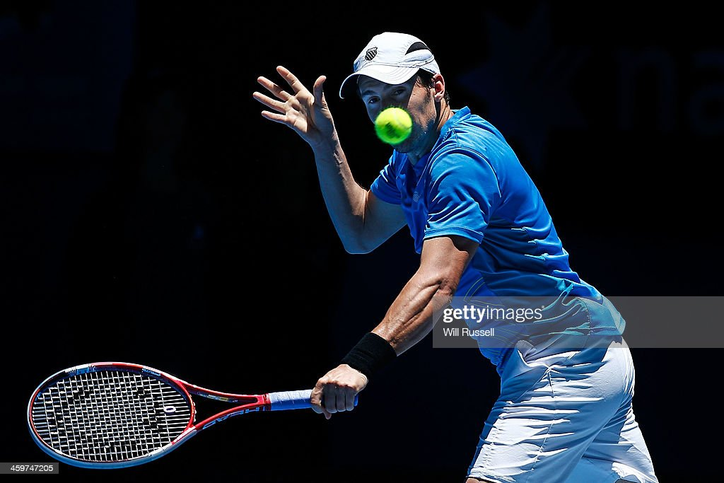 Daniel Munoz-De La Nava of Spain plays a backhand to John Isner of the United States in the men's singles match during day three of the Hopman Cup at Perth Arena on December 30, 2013 in Perth, Australia.