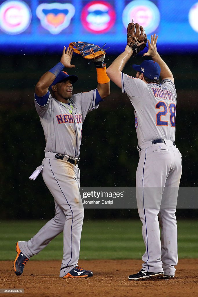 Daniel Murphy #28 and Curtis Granderson #3 of the New York Mets celebrate after defeating the Chicago Cubs in game three of the 2015 MLB National League Championship Series at Wrigley Field on October 20, 2015 in Chicago, Illinois. The Mets defeated the Cubs with a score of 5 to 2.