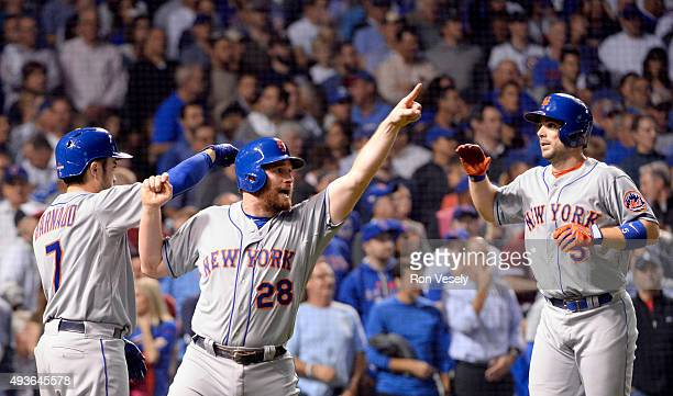 Daniel Murphy and David Wright of the New York Mets celebrate after scoring on Lucas Duda's twoRBI double in the second inning of Game 4 of the NLCS...