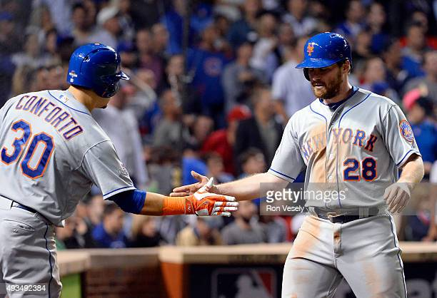 Daniel Murphy and Michael Conforto of the New York Mets celebrate a run in the seventh inning during Game 3 of the NLCS against the Chicago Cubs at...