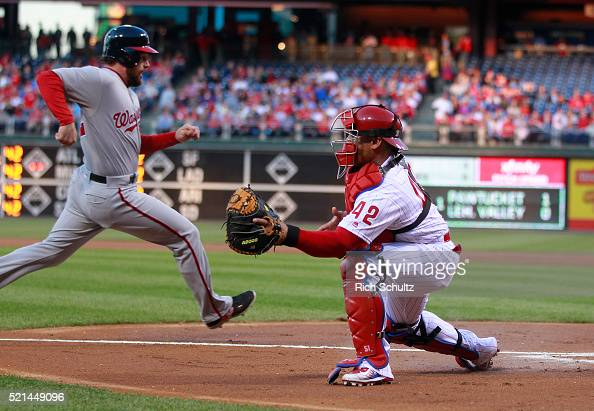 Daniel Murphy left of the Washington Nationals scores on a bases loaded double by Jayson Werth as catcher Carlos Ruiz right of the Philadelphia...