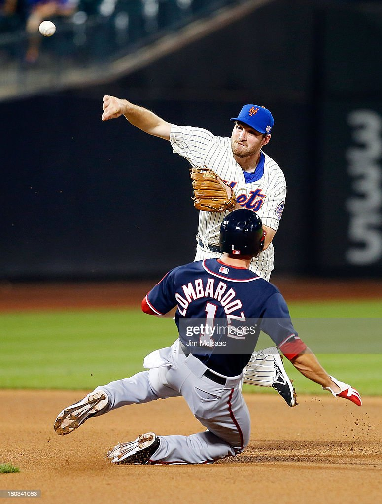 Daniel Murphy #28 of the New York Mets attempts a seventh inning double play after forcing out Stephen Lombardozzi #1 of the Washington Nationals at Citi Field on September 11, 2013 in the Flushing neighborhood of the Queens borough of New York City.