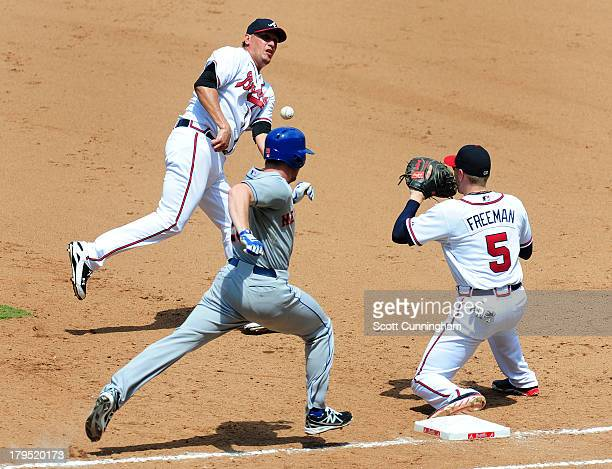 Daniel Murphy of the New York Mets beats the throw to first base by Freddy Garcia of the Atlanta Braves to Freddie Freeman of the Braves at Turner...