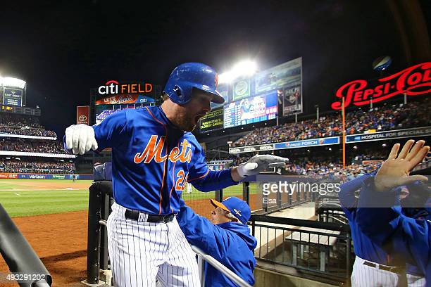Daniel Murphy of the New York Mets celebrates with his teammates after hitting a two run home run in the first inning against Jake Arrieta of the...