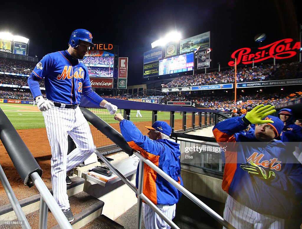 Daniel Murphy of the New York Mets celebrates with his teammates in the dugout after hitting a solo home run in the first inning against Jon Lester...