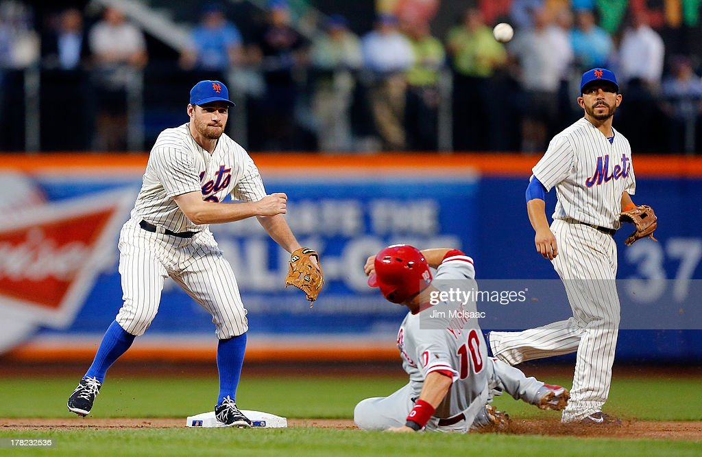 Daniel Murphy #28 of the New York Mets completes a second inning double play after forcing out <a gi-track='captionPersonalityLinkClicked' href=/galleries/search?phrase=Michael+Young+-+Baseball+Player&family=editorial&specificpeople=203149 ng-click='$event.stopPropagation()'>Michael Young</a> #10 of the Philadelphia Phillies at Citi Field on August 27, 2013 in the Flushing neighborhood of the Queens borough of New York City.