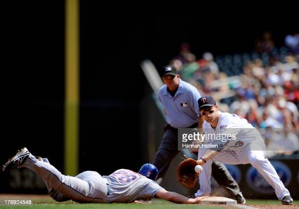 Daniel Murphy of the New York Mets dives back safely to first base as Justin Morneau of the Minnesota Twins fields the ball during the fourth inning...