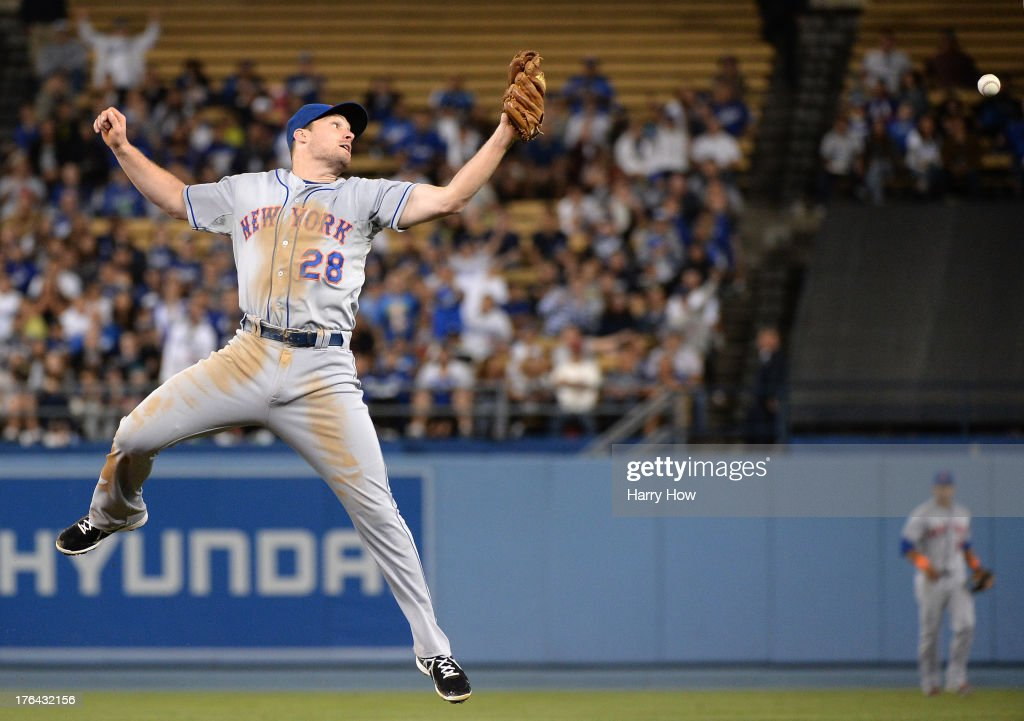 Daniel Murphy #28 of the New York Mets misses a catch off the bat of Mark Ellis #14 of the Los Angeles Dodgers resulting in a single during the sixth inning at Dodger Stadium on August 12, 2013 in Los Angeles, California.