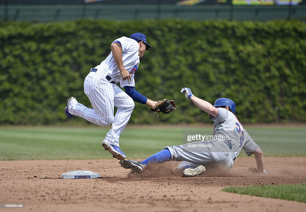 Daniel Murphy #28 of the New York Mets (R) slides safely into second base past second baseman Darwin Barney #15 of the Chicago Cubs advancing after hitting into a fielder's choice during the third inning on May 19, 2013 at Wrigley Field in Chicago, Illinois. Juan Lagares #12 of the New York Mets was caught in a run-down between second and third and thrown out.