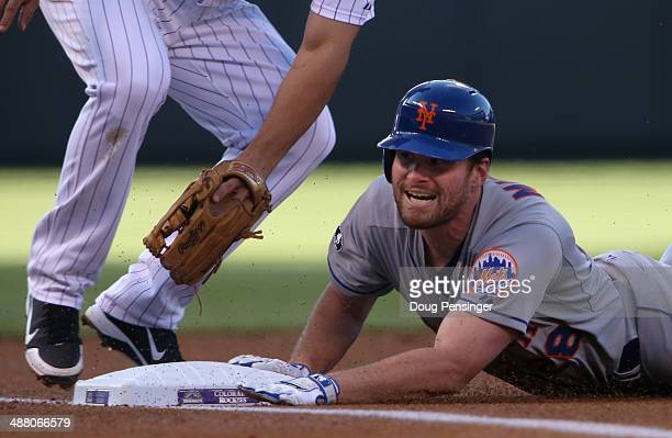Daniel Murphy of the New York Mets slides safely into third base with a triple off of starting pitcher Franklin Morales of the Colorado Rockies in...