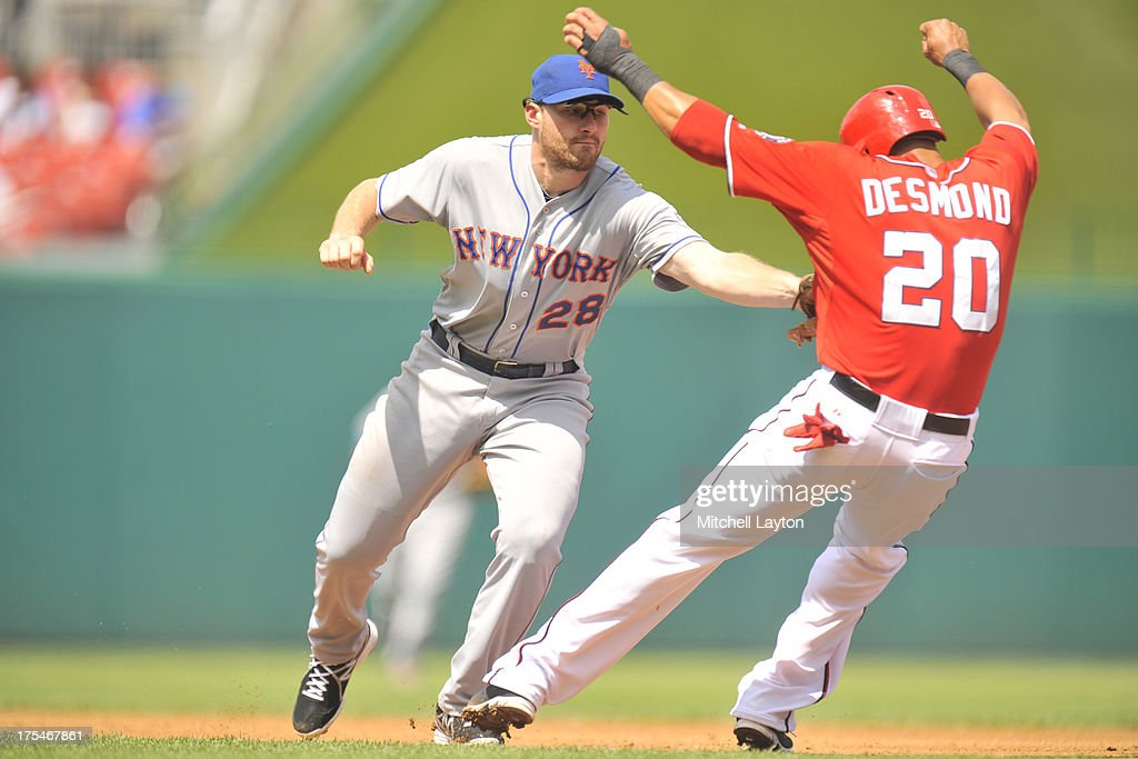 Daniel Murphy #28 of the New York Mets tags out <a gi-track='captionPersonalityLinkClicked' href=/galleries/search?phrase=Ian+Desmond&family=editorial&specificpeople=835572 ng-click='$event.stopPropagation()'>Ian Desmond</a> #20 of the Washington Nationals during a baseball game on July 26, 2013 at Nationals Park in Washington, DC. The Mets won 11-1.