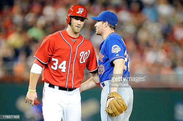 Daniel Murphy of the New York Mets talks with Bryce Harper of the Washington Nationals after they collide in the first inning at Nationals Park on...