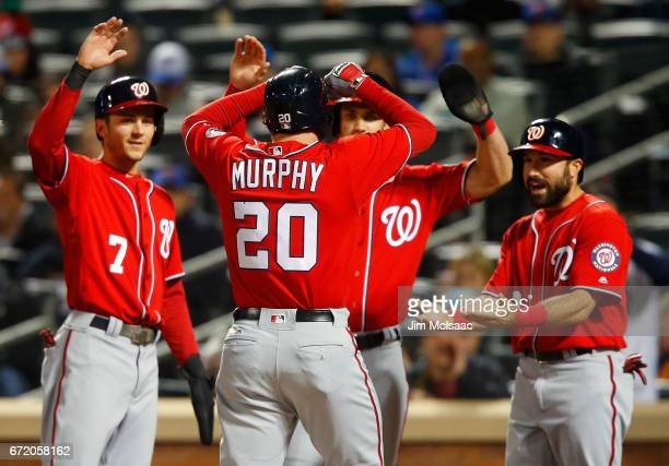 Daniel Murphy of the Washington Nationals celebrates his firstinning grand slam home run against the New York Mets with teammates Trea Turner Bryce...