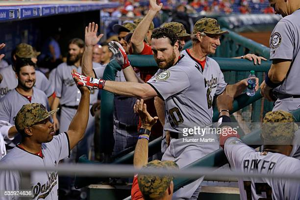 Daniel Murphy of the Washington Nationals is greeted by teammates in the dugout after hitting a solo home run in the fourth inning during a game...