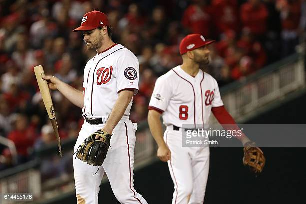 Daniel Murphy of the Washington Nationals retrieves the broken bat of Howie Kendrick of the Los Angeles Dodgers in the seventh inning during game...