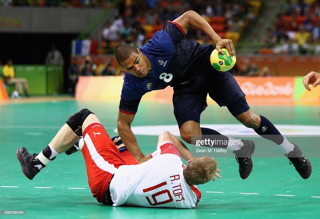 Daniel Narcisse of France handles the ball against Rene Toft Hansen of Denmark during the first half in the Men's Gold Medal Match between Denmark...