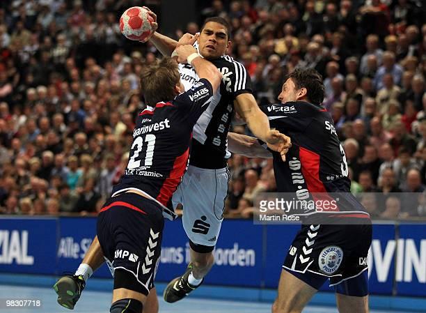 Daniel Narcisse of Kiel challenges Jacob Heinl and Tobias Karlsson of FlensburgHandewitt for the ball during the Toyota Handball Bundesliga match...