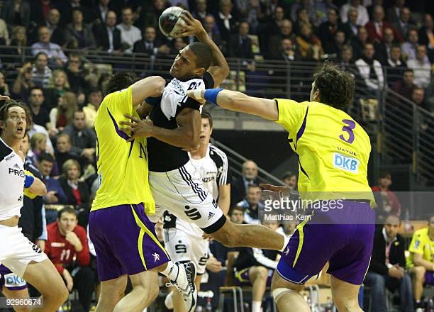 Daniel Narcisse of Kiel is attacked by Michal Kubisztal of Berlin and Stian Fredrik Vatne during the Toyota Handball Bundesliga match between Fuechse...