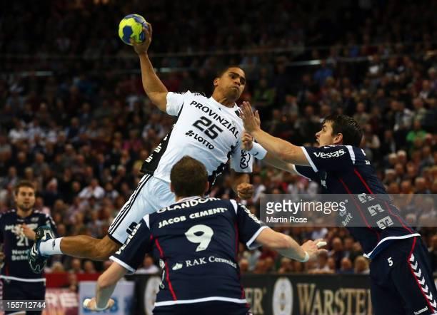 Daniel Narcisse of Kiel is challenged by Arnor Atlason of Flensburg during the DKB Handball Bundesliga match between THW Kiel and SG...