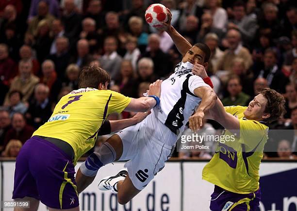 Daniel Narcisse of Kiel shoots at goal against Rico Goede and Runar Karason of Berlin during the Toyota Handball Bundesliga match between THW Kiel...