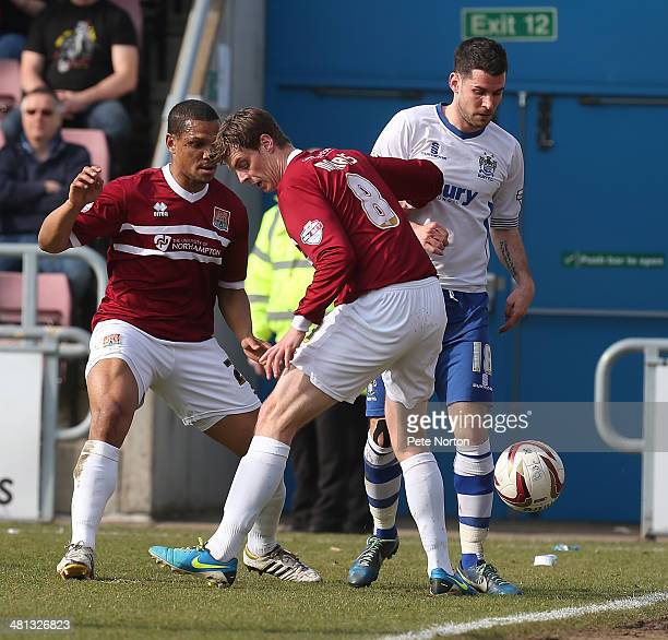 Daniel Nardiello of Bury contests the ball with Ian Morris of Northampton Town as Mathias KouoDoumbe looks on during the Sky Bet League Two match...