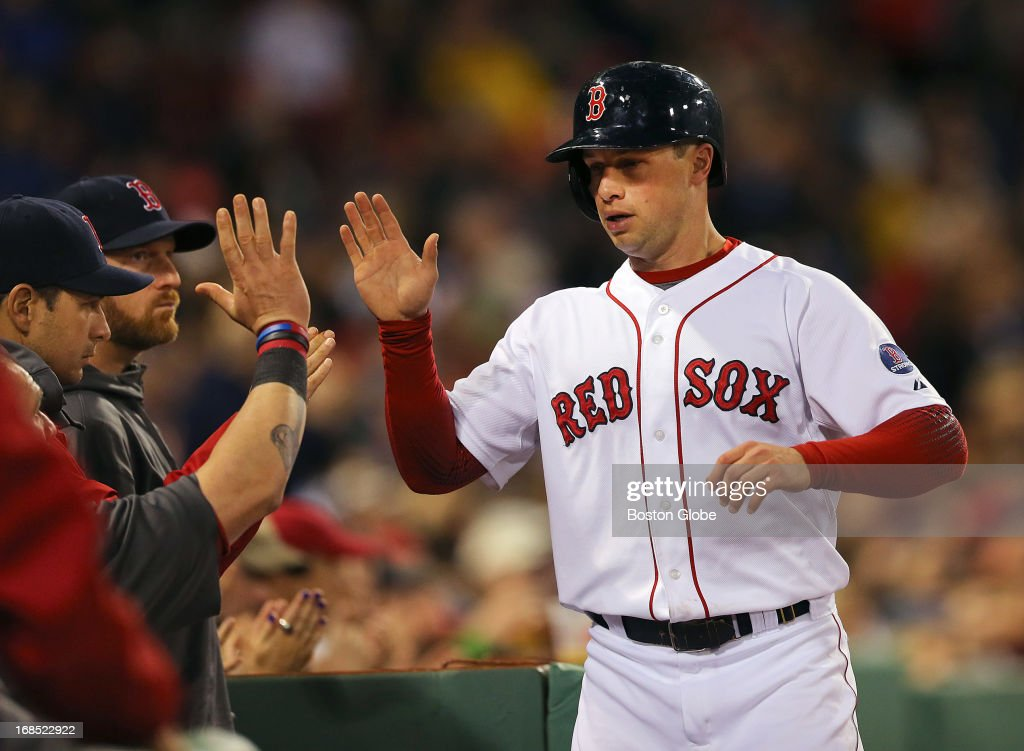 Daniel Nava is congratulated at the Red Sox dugout after scoring on a fourth inning single by Stephen Drew. The Boston Red Sox played the Minnesota Twins at Fenway Park on May 9, 2013.