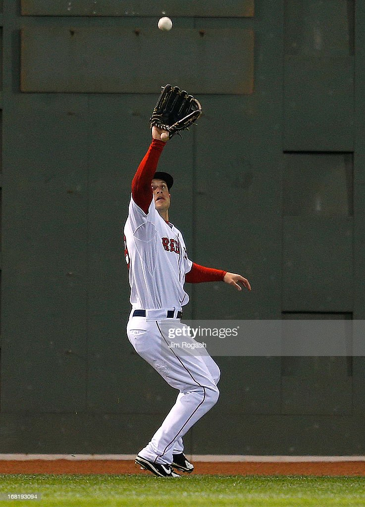 Daniel Nava #29 of the Boston Red Sox catches a sacrifice fly by Justin Morneau #33 of the Minnesota Twins, which scored a run, in the 5th inning the at Fenway Park on May 6, 2013 in Boston, Massachusetts.