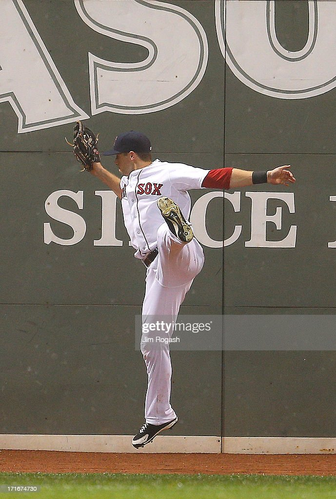 Daniel Nava #29 of the Boston Red Sox makes leaping catch on a ball hit by Edwin Encarnacion #10 of the Toronto Blue Jays in the 8th inning at Fenway Park on June 27, 2013 in Boston, Massachusetts.