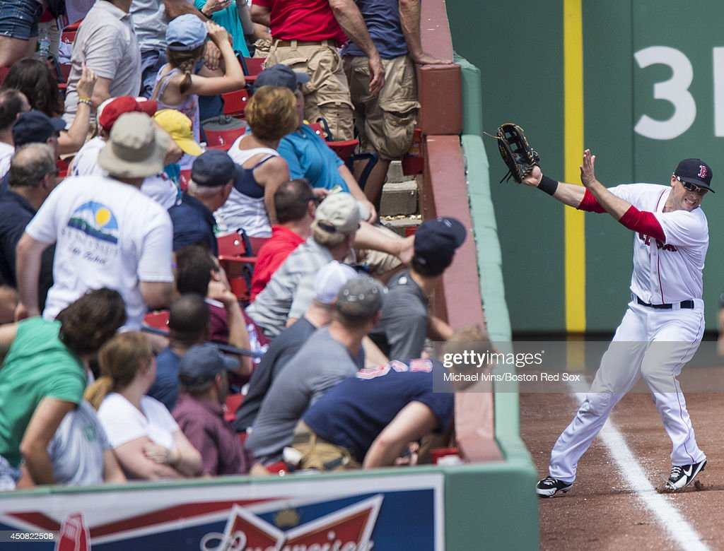 Daniel Nava #29 of the Boston Red Sox runs into the wall while tracking a foul ball against the Minnesota Twins in the second inning at Fenway Park on June 18, 2014 in Boston, Massachusetts.