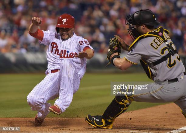 Daniel Nava of the Philadelphia Phillies goes into his slide before getting tagged out at home plate by Francisco Cervelli of the Pittsburgh Pirates...