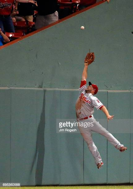 Daniel Nava of the Philadelphia Phillies makes leaping catch on a ball hit by Jackie Bradley Jr #19 of the Boston Red Sox in the tenth inning for the...