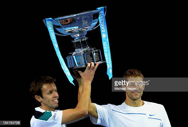 Daniel Nestor of Canada and Max Mirnyi of Belarus lift the trophy following their victory during the men's doubles final match against Mariusz...