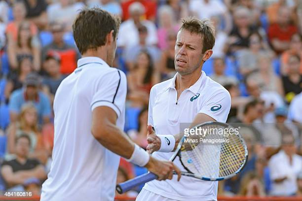 Daniel Nestor of Canada encourages teammate Edouard RogerVasselin of France in their match against Novak Djokovic of Serbia and teammate Janko...