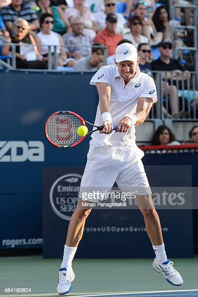 Daniel Nestor of Canada hits a return against Novak Djokovic of Serbia and teammate Janko Tipsarevic during day six of the Rogers Cup at Uniprix...