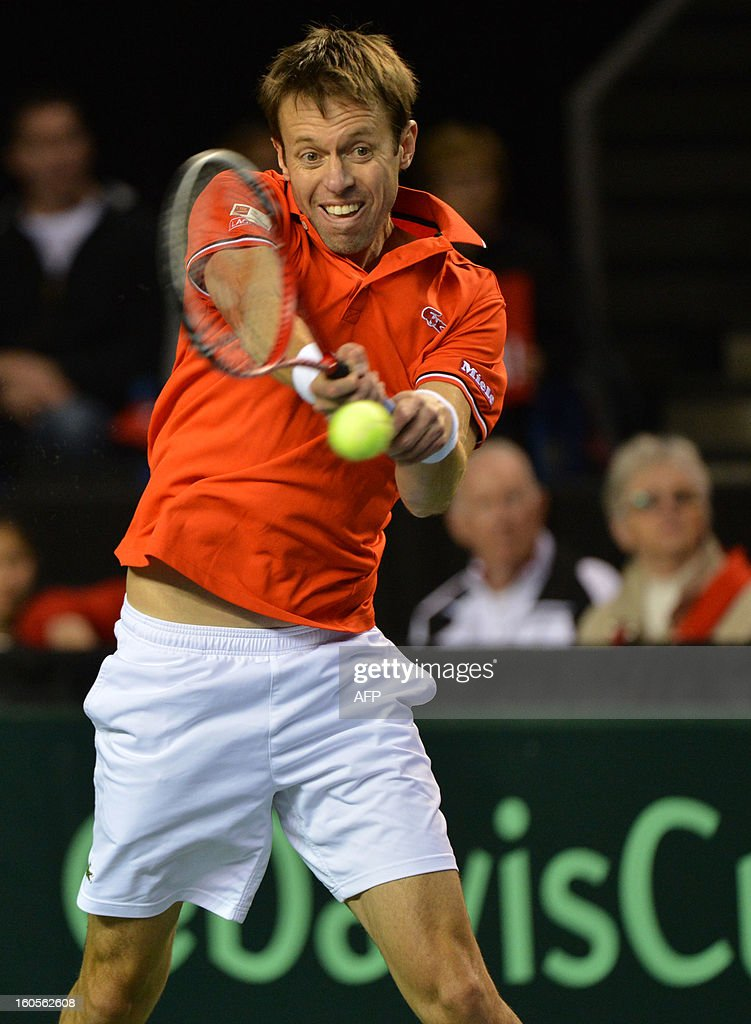 Daniel Nestor of Canada hits a return to Marcel Granollers and Marc Lopez of Spain during a Davis Cup World Group Doubles Rubber, February 2, 2013, at the Doug Mitchell Thunderbird Sports Centre, in Vancouver, BC. AFP PHOTO / Don MACKINNON