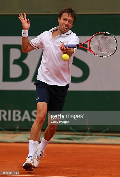 Daniel Nestor of Canada plays a backhand during his Men's Doubles match with Robert Lindstedt of Sweden against Sergiy Stakhovsky of Ukraine and...