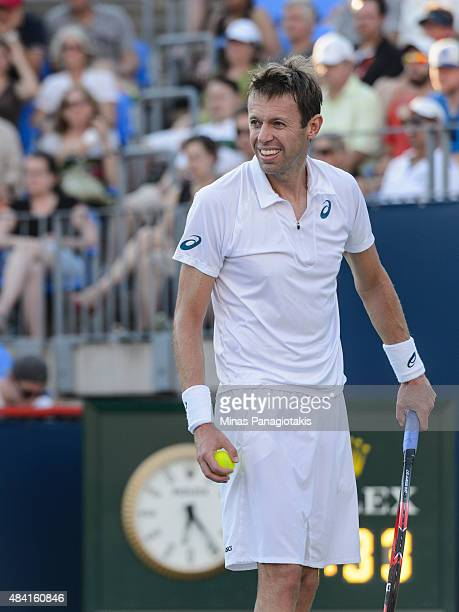 Daniel Nestor of Canada prepares to serve against Novak Djokovic of Serbia and teammate Janko Tipsarevic during day six of the Rogers Cup at Uniprix...