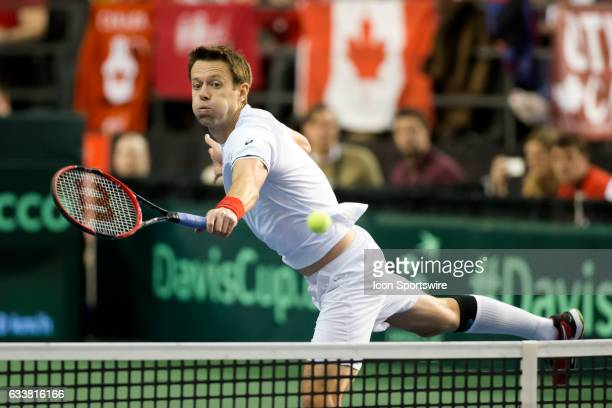 Daniel Nestor of Canada volleys the ball back against Dominic Inglot and Jamie Murray of Great Britain in men's doubles play during the Davis Cup...