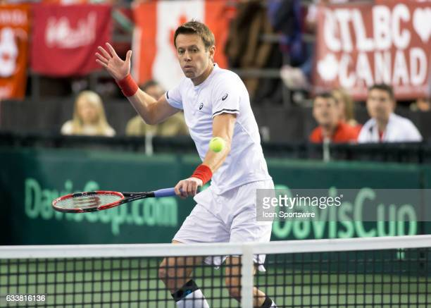 Daniel Nestor of Canada volleys the ball back to Dominic Inglot and Jamie Murray of Great Britain in men's doubles play during the Davis Cup first...