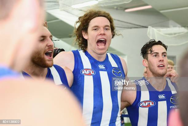 Daniel Nielson Ben Brown and Declan Mountford of the Kangaroos sing the song in the rooms after winning the round 19 AFL match between the North...