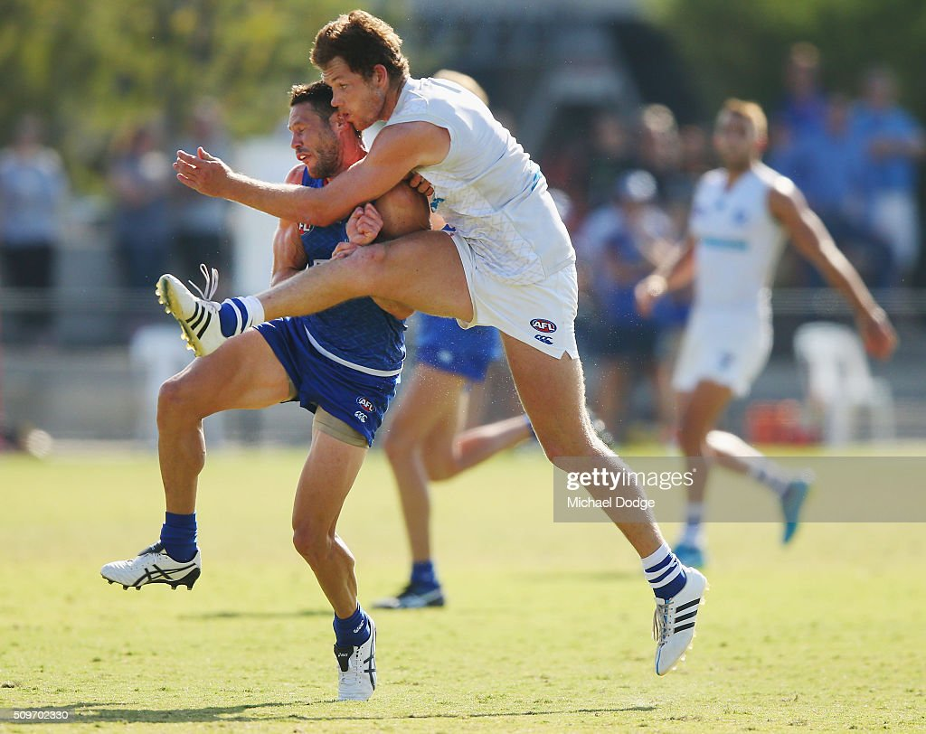 Daniel Nielson kicks the ball for a goal while clashing heads with Sam Gibson of the Kangaroos during the North Melbourne AFL Intra-Club match at Arden Street Ground on February 12, 2016 in Melbourne, Australia.