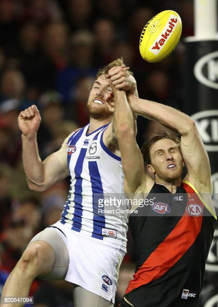 Daniel Nielson of the Kangaroos and James Stewart of the Bombers compete for the ball during the round 18 AFL match between the Essendon Bombers and...
