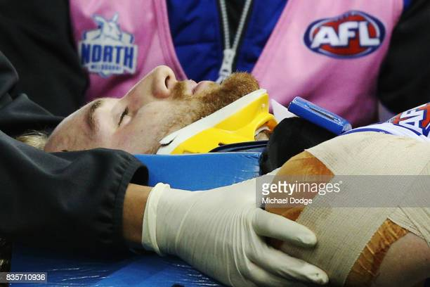 Daniel Nielson of the Kangaroos was crunched in a contest and is taken off on a stretcher during the round 22 AFL match between the St Kilda Saints...