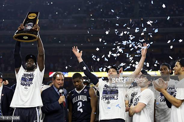 Daniel Ochefu of the Villanova Wildcats hoists the trophy after the Villanova Wildcats defeat the North Carolina Tar Heels 7774 to win the 2016 NCAA...