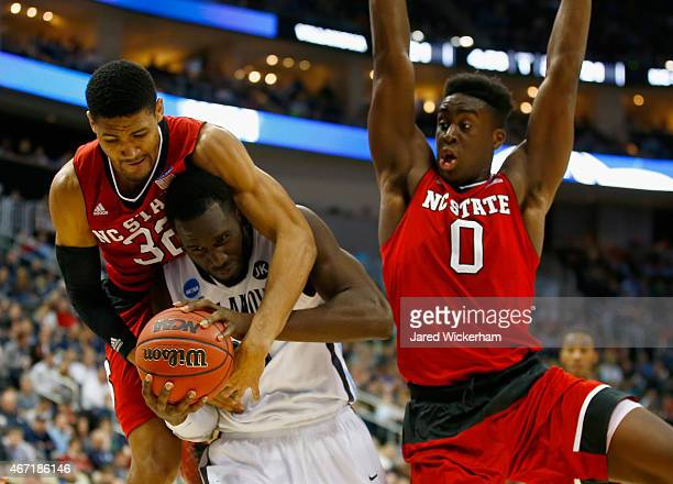 Daniel Ochefu of the Villanova Wildcats is pressured by Kyle Washington and AbdulMalik Abu of the North Carolina State Wolfpack in the first half...