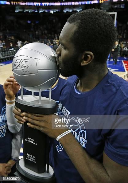 Daniel Ochefu of the Villanova Wildcats kisses the Big East regular Season Championship trophy after defeating the Georgetown Hoyas 8471 in an NCAA...